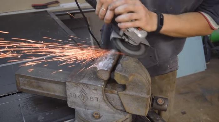 Тиски ранее часто использовались как наковальня, поэтому выравниваем болгаркой верхнюю часть. | Фото: youtube.com.