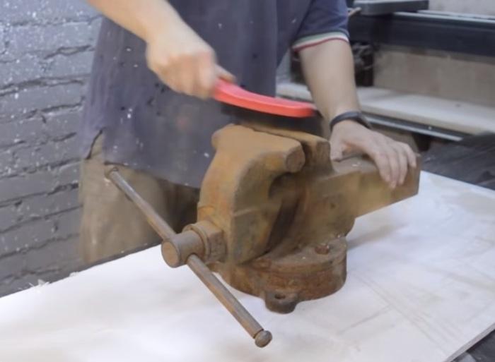 Сперва обрабатываем поверхность тисков металлической щеткой. | Фото: youtube.com.