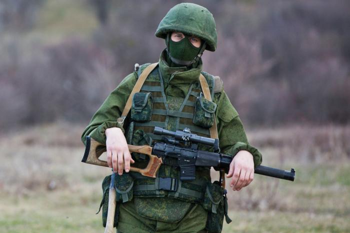 Снайпер в камуфляже и с винтовкой.
