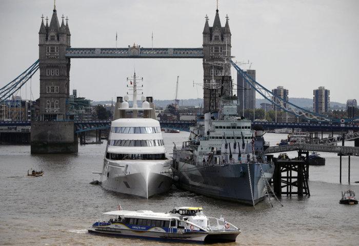 Моторная яхта «А» на реке Темза, рядом с британским крейсером HMS Belfast.