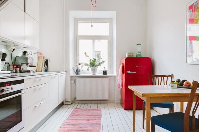 Интерьер маленькой кухни с холодильником необычного цвета.