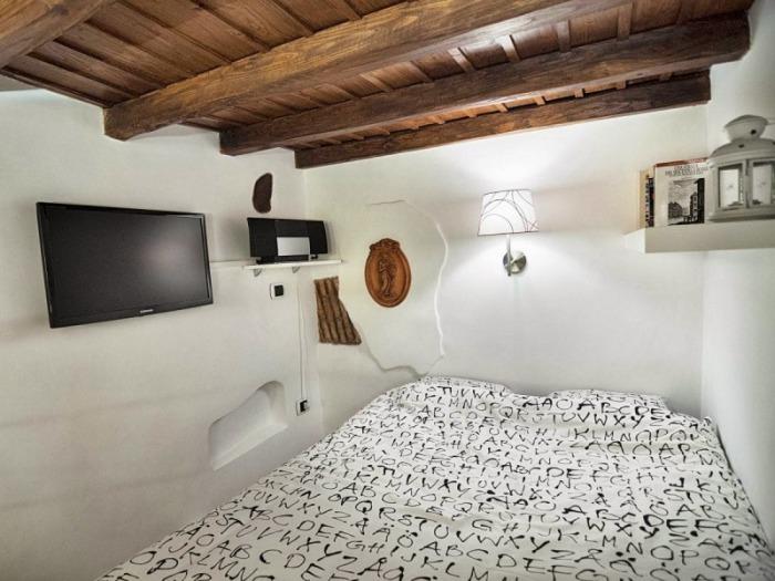 Необычный потолок преображает дизайн маленькой спальни.