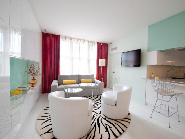 Белый глянцевый шкаф увеличивает маленькую гостиную.