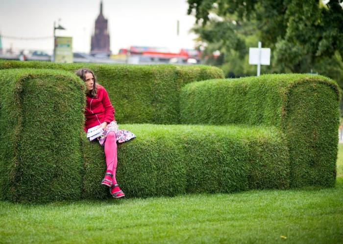 Мягкая скамейка, увитая растениями.