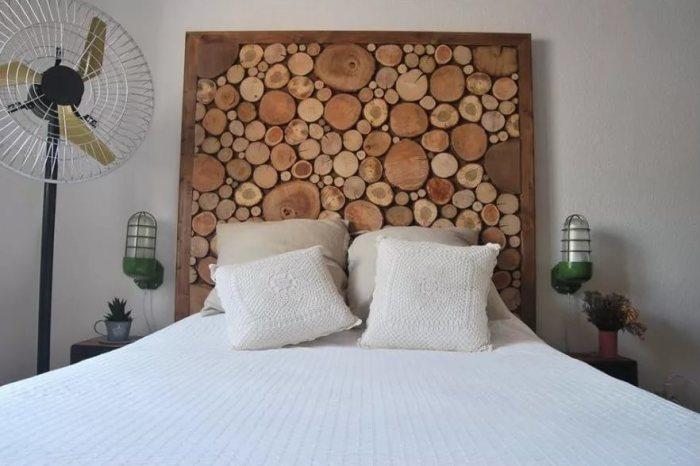 Декор изголовья кровати при помощи деревянных спилов.
