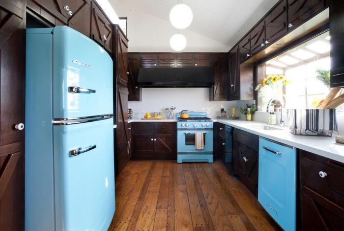 Темний інтер'єр кухні оживає за рахунок яскравої і блискучою техніки.