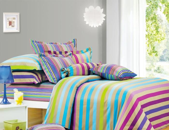Яркое постельное белье оживит интерьер спальни.