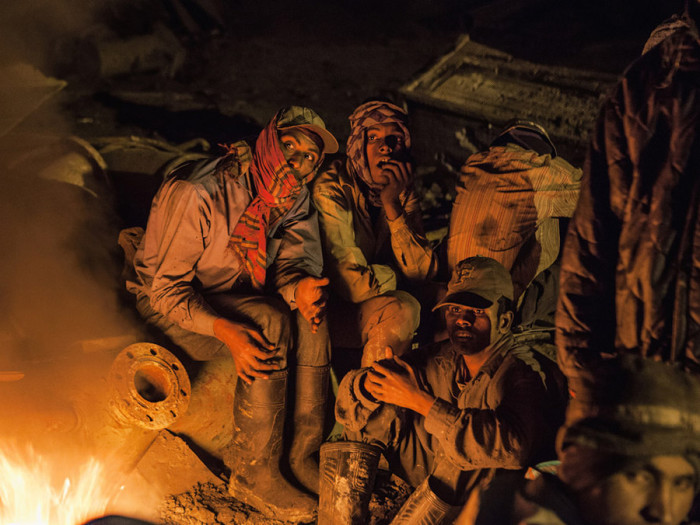 Рабочие греются у костра не думая о том, что резина которую они жгут - ядовита.