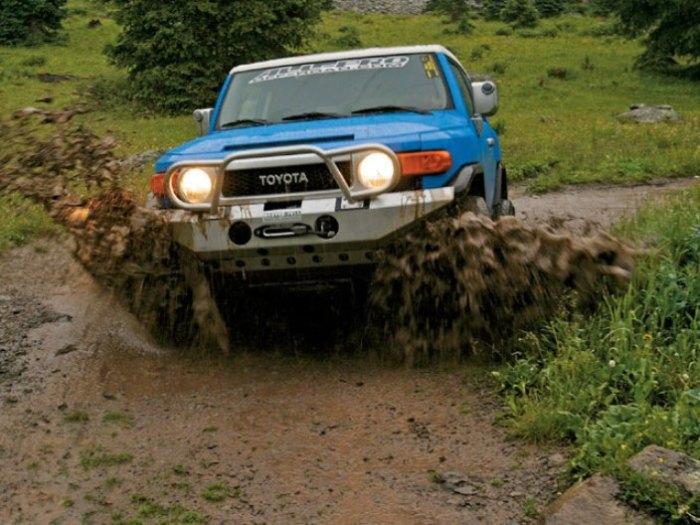 Лихо по грязи едет Toyota FJ Cruiser.