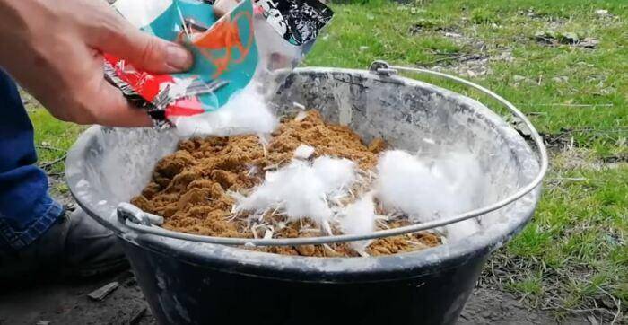 Мешаем сухой раствор с пластификатором. /Фото: youtube.com.
