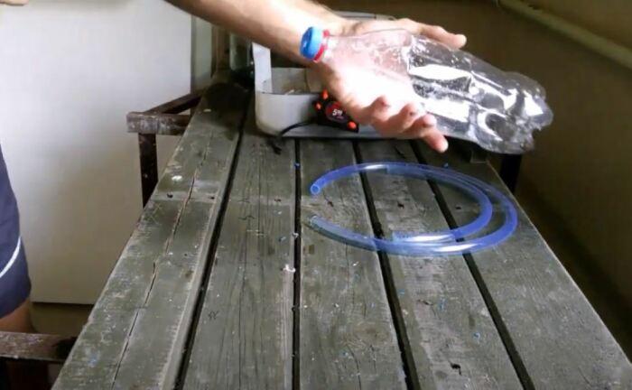Разрезаем шланг на две части и делаем отверстия в бутылке. /Фото: youtube.com.