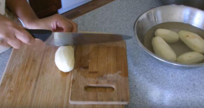 Чистим картошку, укладываем доски и делаем надрезы. /Фото: youtune.com.
