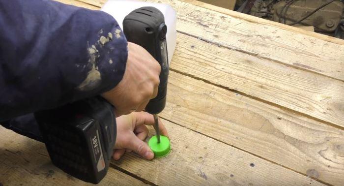 Сверлим крышку под провод. /Фото: youtube.com.