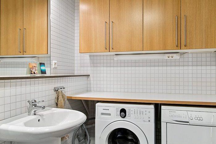 В небольшой комнате удалось разместить системы хранения и сразу две стиральные машинки.