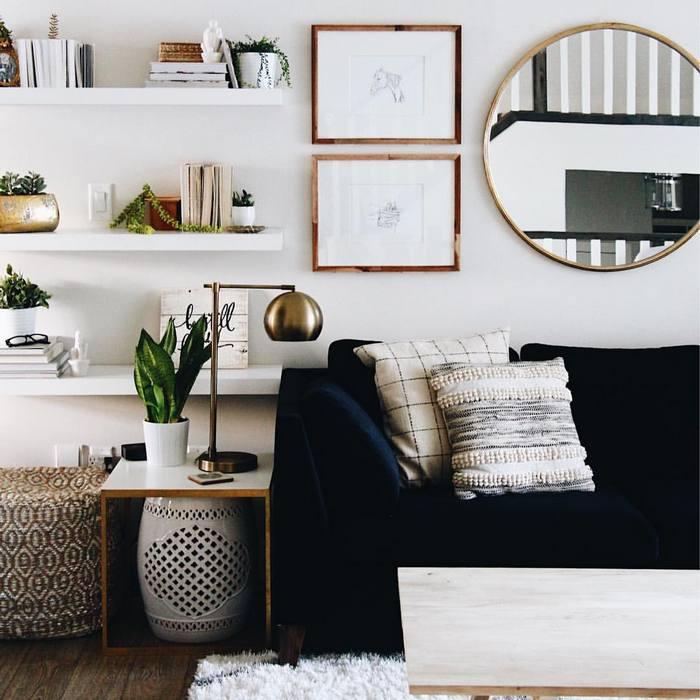 Стильное круглое зеркало в интерьере маленькой гостиной.