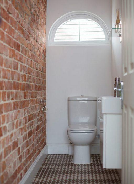 Кирпичная стена в маленьком туалете.