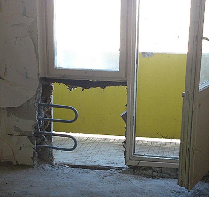 Демонтаж подоконного блока с батареями в стене. | Фото: slom-servis.ru