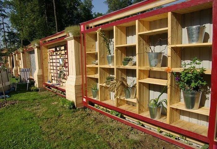 С внешней стороны забор из металлочерепицы, а внутри деревянные полки для горшков с цветами и для других хозяйственных назначений.