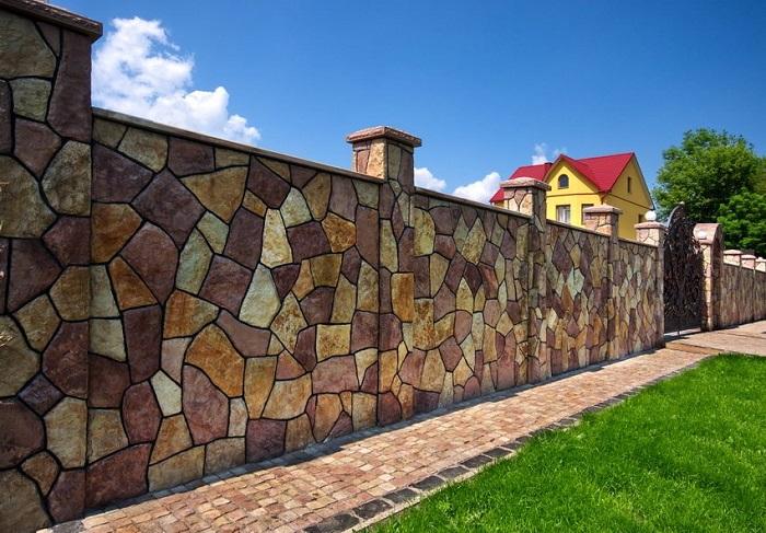 С виду забор из разных цветных камней, но нет. Это просто на бетоне сделали дизайн дикого разноцветного камня различных размеров.