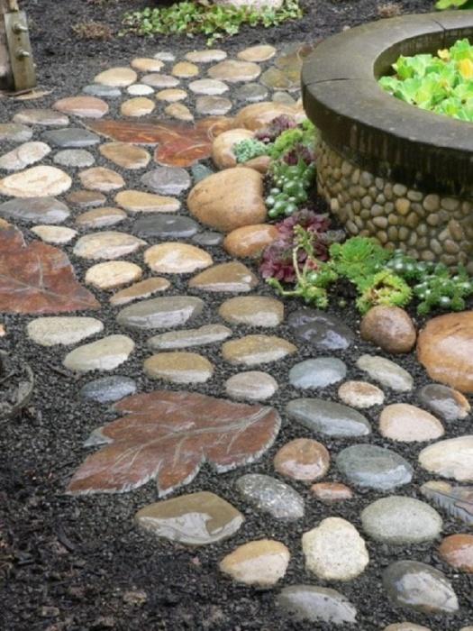 Основанием является обыкновенная насыпь для дорожки, а украшение её камни, галька, а также сделанные собственноручно листики из бетона.