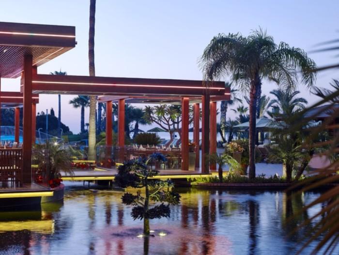 Вокруг красивейшего в Лимассоле бассейна Four Seasons расположены кафе и бары отеля, лежаки и гамаки, клумбы и пальмы.
