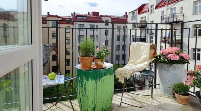 Старенький раскладной стул, бочка, имитирующая стол, горшки с цветами, любимый плед - идеальный вариант для декора балкона.