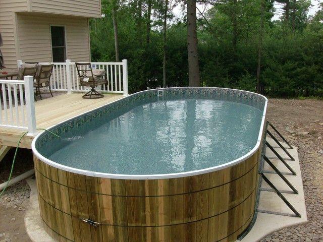 Овальный каркасный бассейн смонтирован у деревянной веранды.