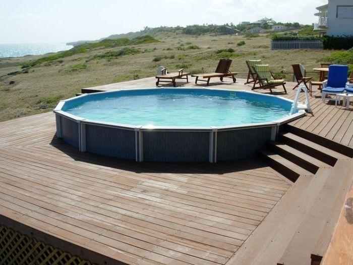Всесезонный каркасный бассейн с деревянным помостом вокруг.