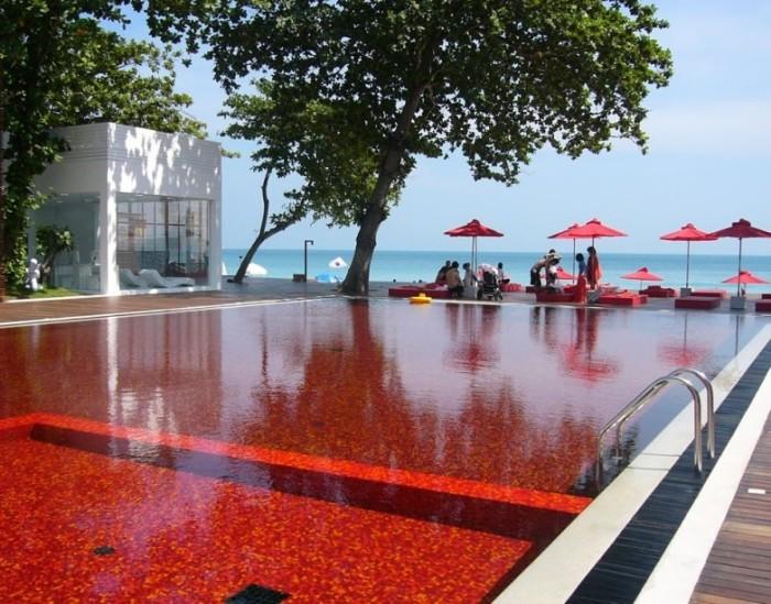 Красный цвет бассейна получается в результате сочетания красной, желтой и оранжевой плитки, из которой сделан сам бассейн.
