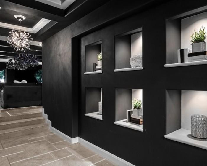 Чёрные стены прихожей с белыми нишами для хранения вещей.