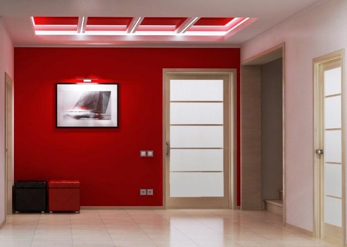 Красная акцентная стена в прихожей в сочетании со светлым полом и дверьми – идеальное цветовое решение.