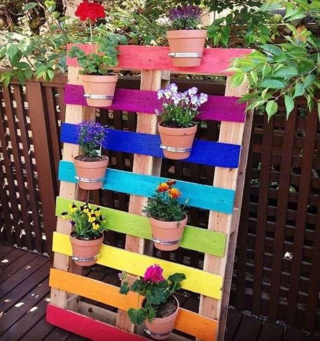 Использовав такие нехитрые материалы, как деревянный поддон, металлические хомуты и глиняные горшки с цветами, можно создать настоящее произведение искусства.