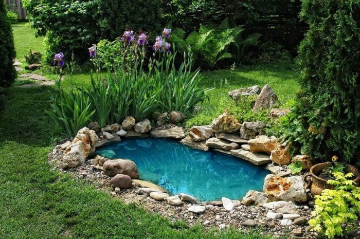Небольшой искусственный пруд на даче с чистой голубой водой.