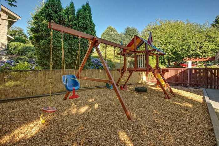 Желательно, чтобы детская площадка имела специальное мягкое покрытие. Измельченная кора дерева отлично подойдет для этих целей.