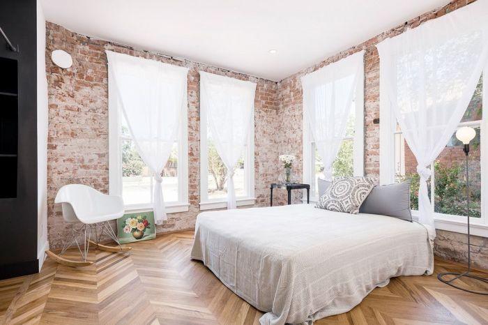 Белые полупрозрачные шифоновые занавески смотрятся очень стильно на фоне кирпичных стен.