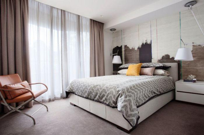 Современная спальня с тёмными плотными шторами в пол.