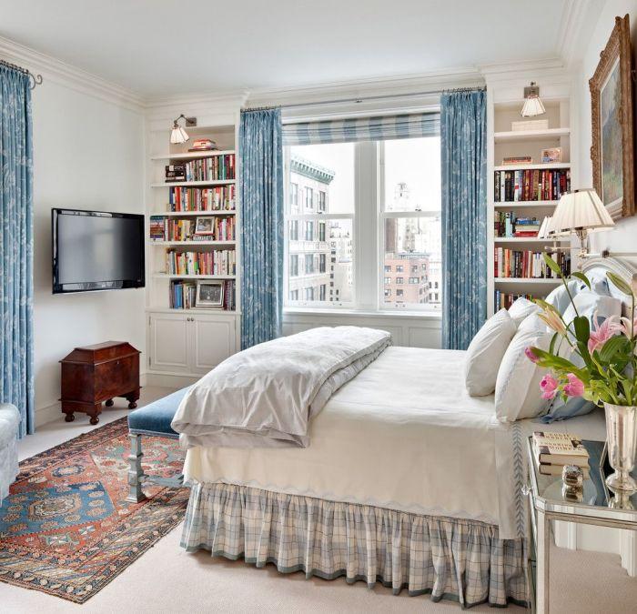 Классические голубые шторы с рисунком в сочетании с римскими шторами в уютной светлой спальне.