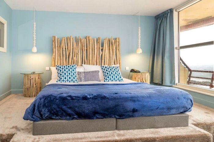 Для спальни морской тематики подойдут голубые шторы по длине окна.