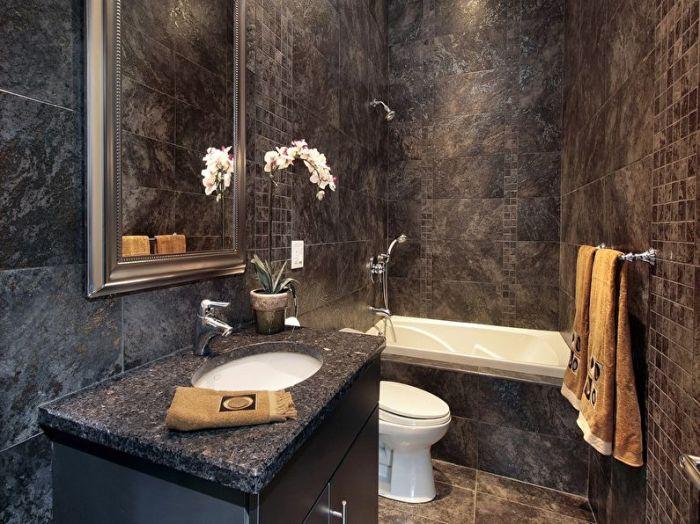 Ванная, выполненная в тёмных тонах и оттенках с имитацией под камень.