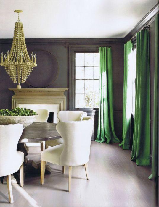 Нефритовые шторы разбавляют серый интерьер гостиной.