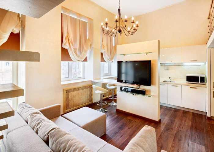 Зонирование кухни и гостиной небольшой перегородкой с полочкой под телевизор.