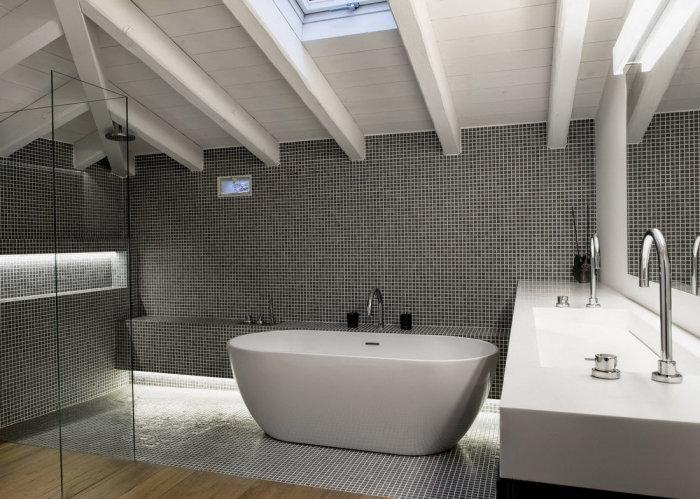 Серые стены из мелкой мозаики прекрасно смотрятся в ванной комнате.
