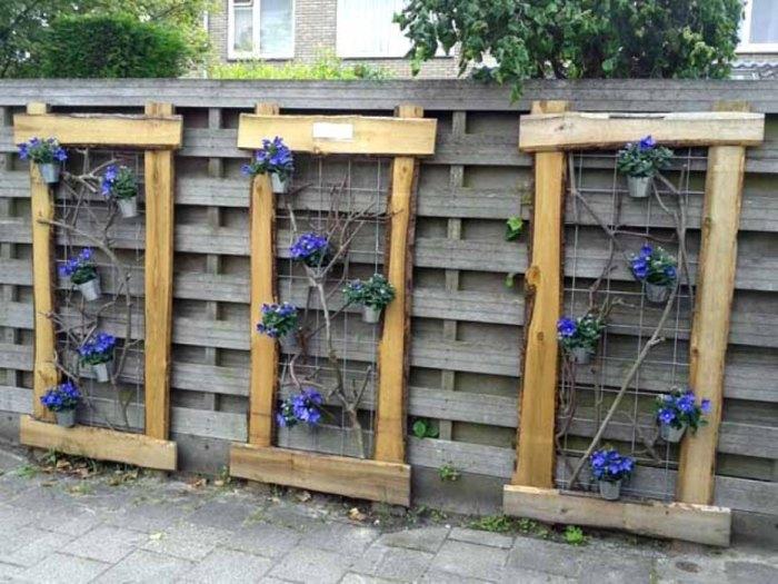 Самое простое и интересное решение - повесить на забор горшки, которые будут служить прекрасным украшением.