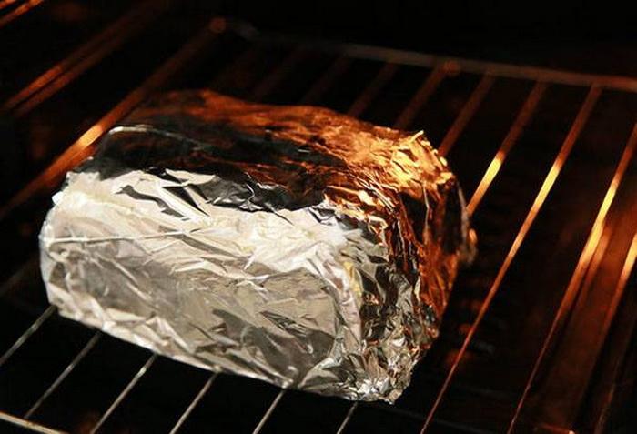 Хлеб нужно завернуть в фольгу и поместить в духовку.