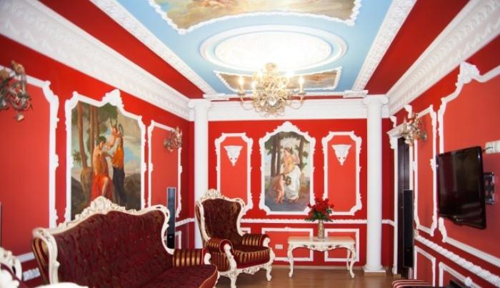 Красная комната с лепниной на стенах.