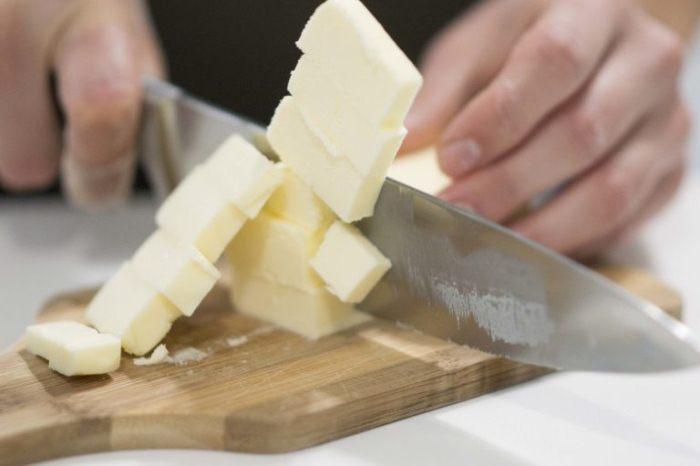 Порезать кусок масла на небольшие кубики.