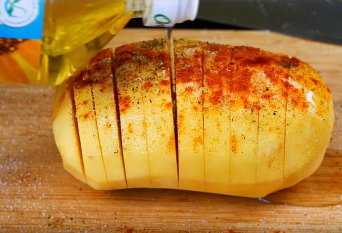 Разрежьте картошку, посолите, присыпьте специями, полейте маслом.