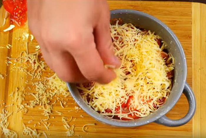 Выкладываем начинку слоями, сверху посыпаем тертым сыром.