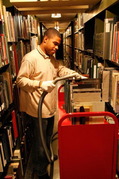 Чистка книг в библиотеке при помощи пылесоса.