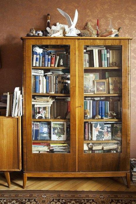 Старый шкаф с книгами и статуэтками.